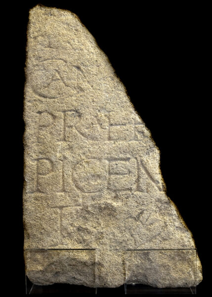 An irregular half of a carved stone slab with incomplete text carved in large letters covering most of it's face
