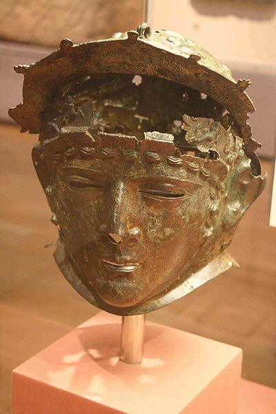 A highly detailed bronze helmet depicting a face with narrow gaps for the wearer to see out through the masks face
