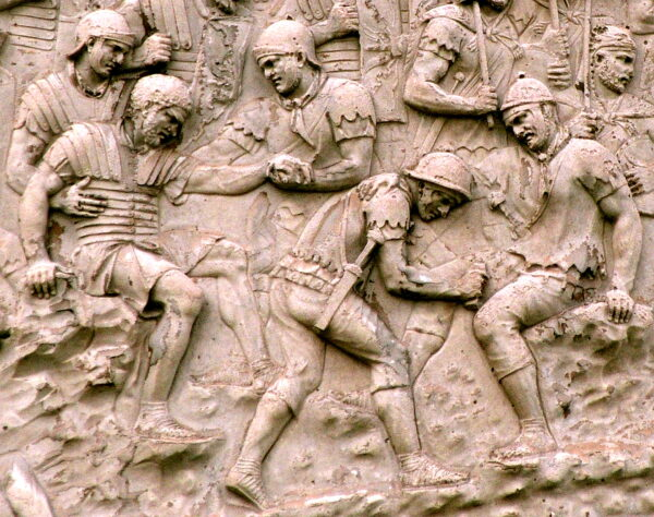 A detailed stone carving showing several injured Roman soliders being given medical assistance and others Roman soldiers standing in the background