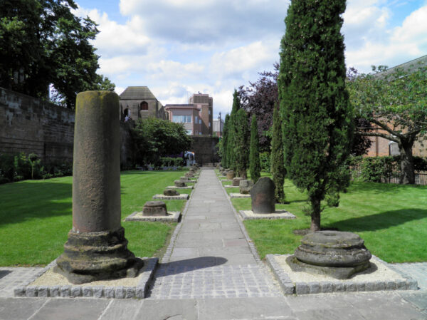 A central blockwork path lined either side by ruined pillars, mostly only a few inches high, and adjacent lawned areas with a variety of borders