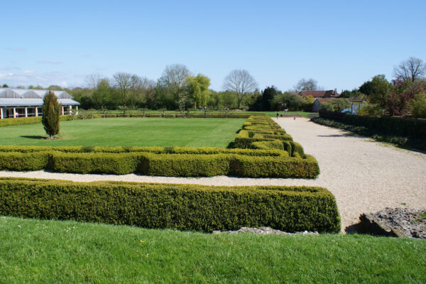A large lawned area surrounded by broad, well kept, low level, topairy hedging and broad gravelled paths - There are also other styles of garden on each side