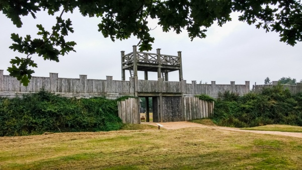A photo showing a gatehouse structure with extensive wooden defensive walls either side