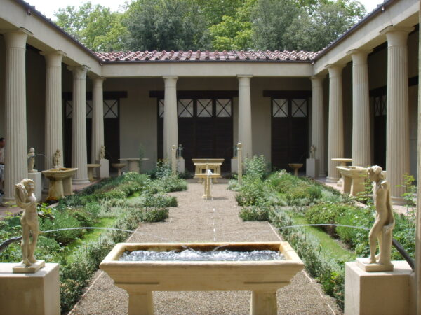 An enclosed courtyard area, with a high columned veranda on all sides - adjacent to these columns are a large number of fountains and statues - within this courtyard there is a broad cross-shaped pathway with formal planting in each quarter