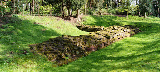 A photo showing an 'L' shaped base of a sustantial stone wall, with grass banks on either side, and tree cover to the left hand side