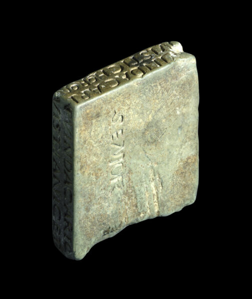 An irregular small stone square collyrium stamp (looks like a thick tile) - this stone is shown at an oblique angle to show carved text along two edges - there is also text carved onto the face of this square