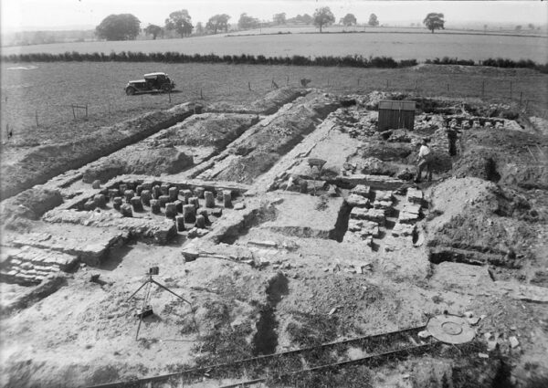 A black and white photo showing a complex of archaeological features - there is also a car parked nearby which gives the photo a reference to its 1930's origin - also in the foreground there is also the end of a narrow gauge railway track