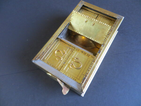 A intracate looking gold coloured metal box with an inset containing five compartments with doors: a central door with two smaller doors on either side - these all appear to be made of similar metalic material - both the inside edges of this box, and the edges of the door-closures, have a crimped pattern - the central compartment, which is open, has a rasied piece inside that resembles a quarter sphere: this is a bowl/cup on the reverse, used for mixing paste made from a collyrium fragment - each door also appears to have looped handles that resemble an exaggerated Greek Omega symbol