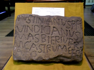 A colour photo showing a slightly irregular carved stone with four lines of Latin text that also seem to be slightly amateur in their presentation