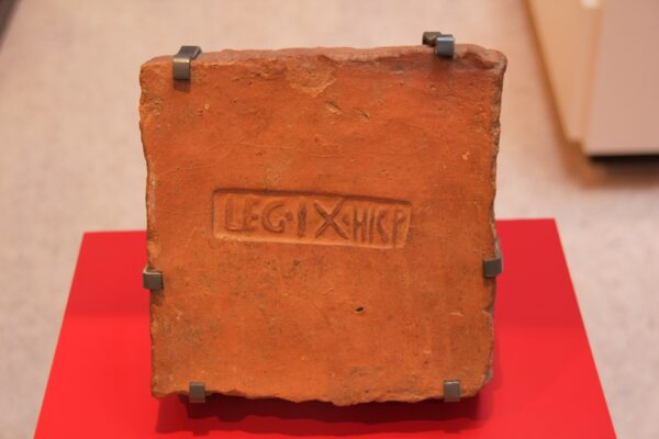 A colour photo of a terracotta roof tile presented on a metal display stand which is clasped in several places along the tiles edge