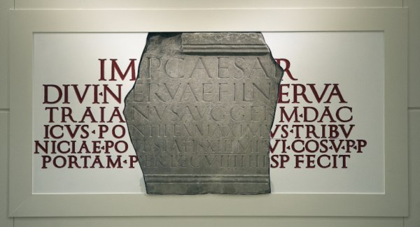 A colour photo showing a fragment of a carved stone inscription - this is set onto a reconstruction of the stone's full text, so that it can be read in its entirety