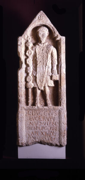 A colour image showing an almost complete carved tombstone of Lucius Duccius Rufinus wearing robes - he is holding his standard in his right hand, and a square object in his left hand - he is standing within an arched alcove with a double stepped impost, and a triangular apex that is decorated with a cross within a circle - below this is a carved inscription - both these have a double inset border