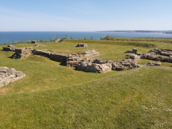 A colour photo showing a well maintained ruin from a cliff top view - there is a range of walls and structures that remain from a fortlet close to Scarborough Castle - there is also a bank that surrounds most of this area