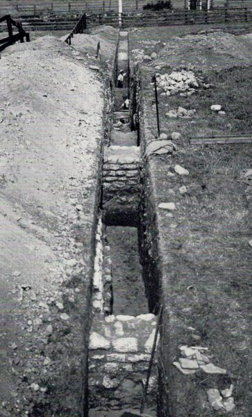 A black and white photo showing a neatly dug, deep trench containing substantial stone walls that intersect this trench - there is an extensive spoil heap on the left hand side, and much small collections of stone of the right hand side - there is also a measuring sticks in the foreground, and another about halfway along the trench - three men can be seen within the trenches, and in the background there is a fence-line along either side of the railway line