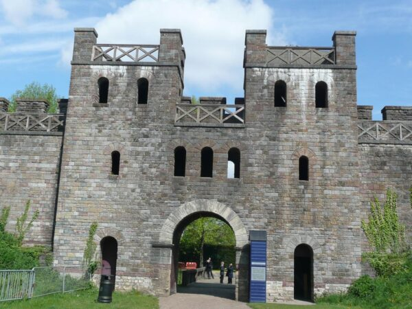 A colour photo showing a large stone built gatehouse with a main entrance gate, plus two much smaller side gates - above this there is a level with three central windows, and two slightly smaller window that mirror the positions as described previously - above this is another level that links to a palisade walkway - and finally above this are two towers on either side of the main gate with another platform placed at the top of each tower - there is also a variety of street furniture such as litter bins, fences and signage