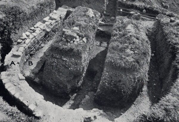 A black and white photo showing the horseshoe shaped wall of an apsidal building and within this is a rectangular shaped earlier building - within this are two mounds of earth with a neatly cut trench running through it - there are a couple of pieces of archaeological equipment on the top left hand side that look like a folded up canvas and a wooden framework