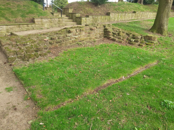 A colour photo showing two interescting walls about five courses high, with an outline on the other two sides of a rectangular area of grass - There is a pathway on the left hand side that turns right along the longest section of wall, and then follows a modern wall that skirts the edge of a grass embankment - there are also steps leading throught this embankment - mature trees are visable in the background