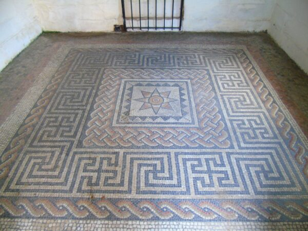 A colour photo showing a Roman mosaic floor - this mosaic has a central star or sun shape within a decorated square - surrounding this are three wide borders of tesserae - this room has white washed walls, and the base of an iron grating is visable against the back wall of this room