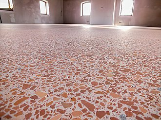 A colour photo showing a example of an opus signinum cast floor, made up of a mixture of broken tiles and mortar making it appear like solid stone - this example uses lots of pieces of terracotta tile